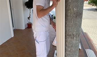 Weiß gestrichenes, dorisches Kapitell an beschichteter Säule